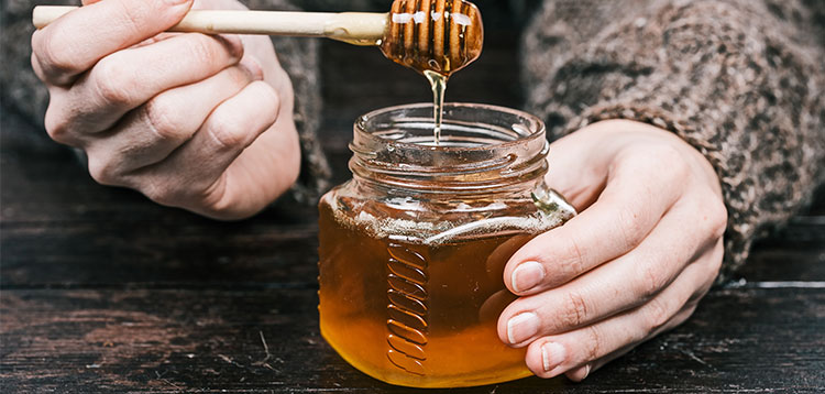 Person holding a honey jar