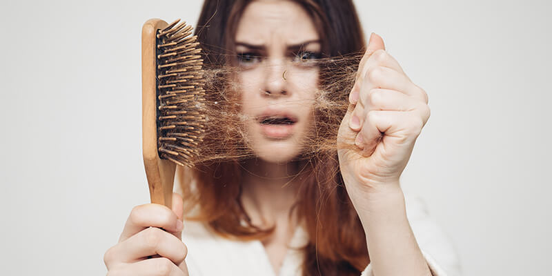 Girl Pulling Hair Out Of A Brush